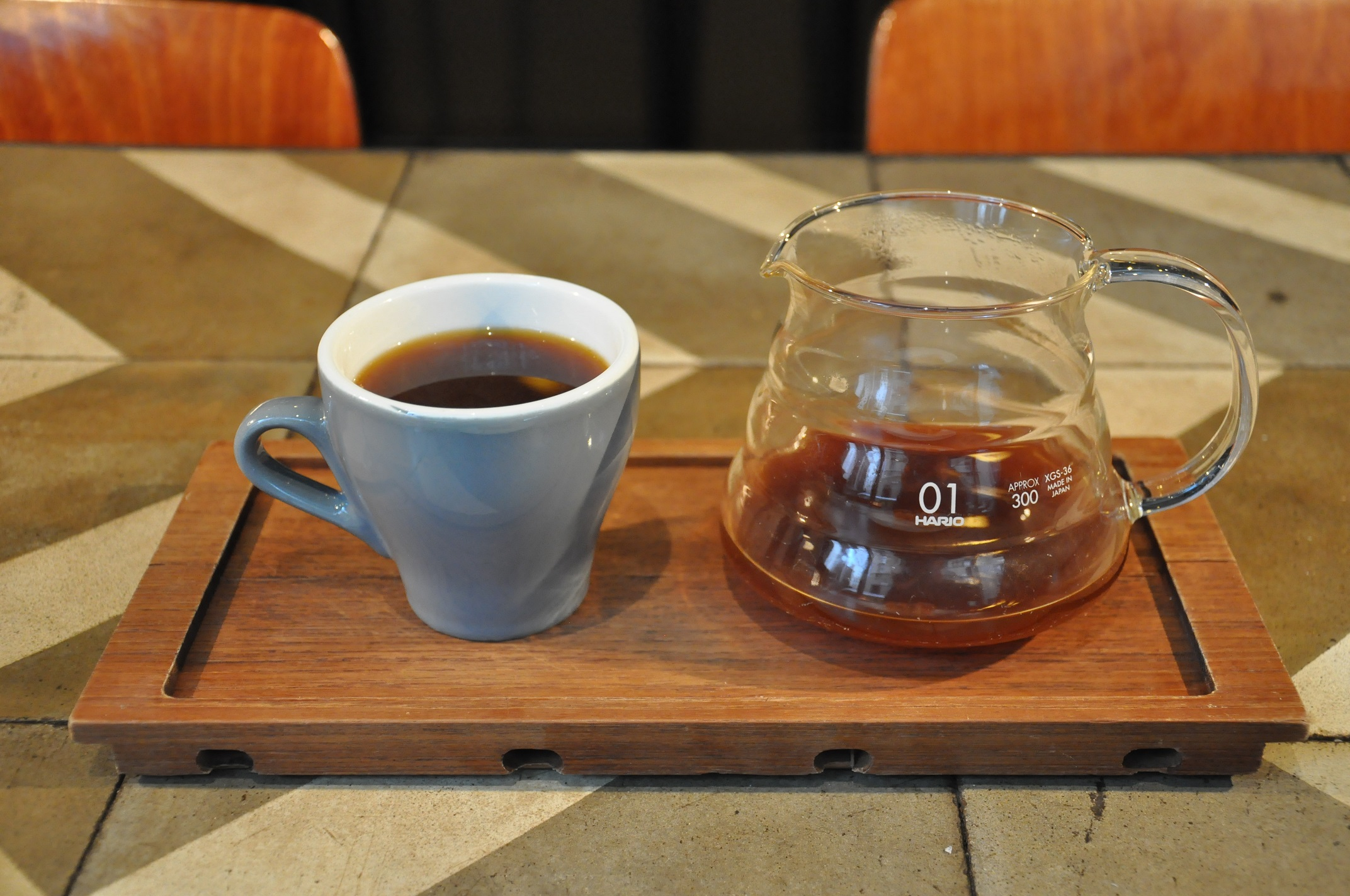 A filter coffee served in a carafe and a tulip-shaped blue cup, presented on a wooden tray.