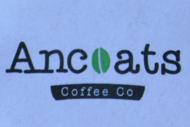 "The Ancoats Coffee Co logo, the ""o"" in Ancoats being replaced with a stylised green coffee bean."