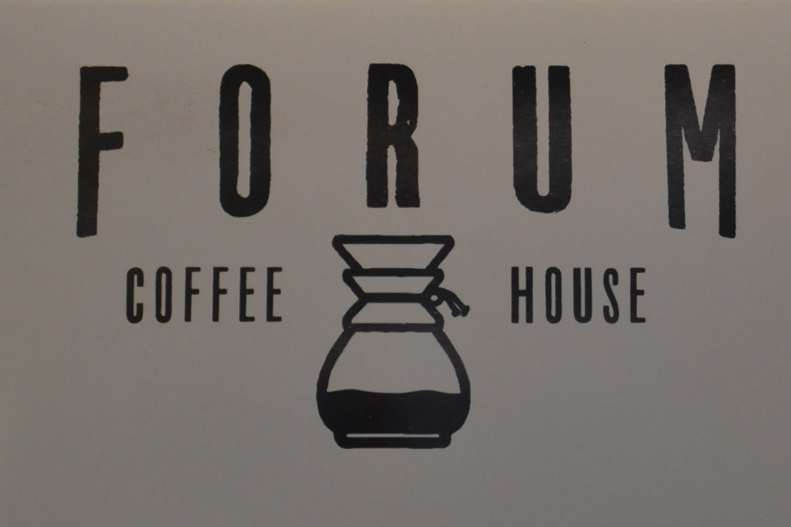 "The Forum Coffee House logo, with a drawing of a Chemex coffee brewer between the words ""Coffee"" and ""House""."