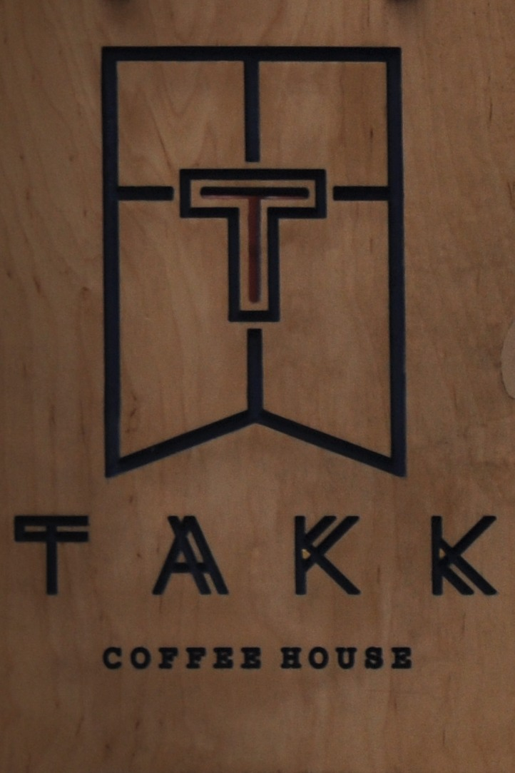 "Detail from the TAKK sign which hangs outside on Tariff Street: the TAKK logo, a cut-out T over the words ""TAKK Coffee House"", etched in wood in black ."
