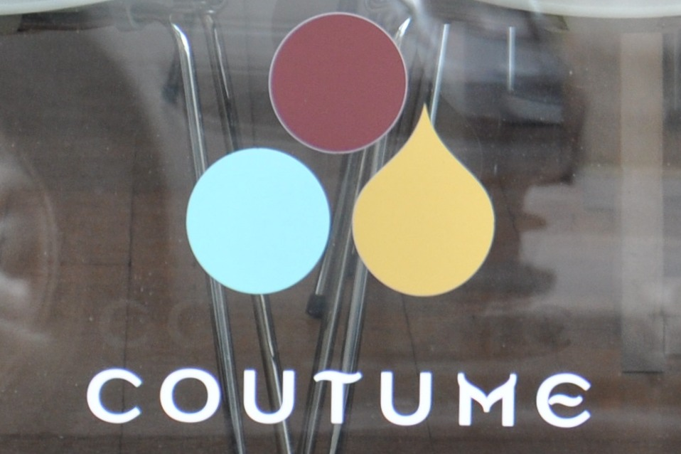 "The Coutume logo painted in the window of Coutume Instituutti: a red circle, blue circle and yellow tear-drop in a triangular arrangement above the word ""Coutume"". The red circle is at the top, the blue circle and tear-drop below."