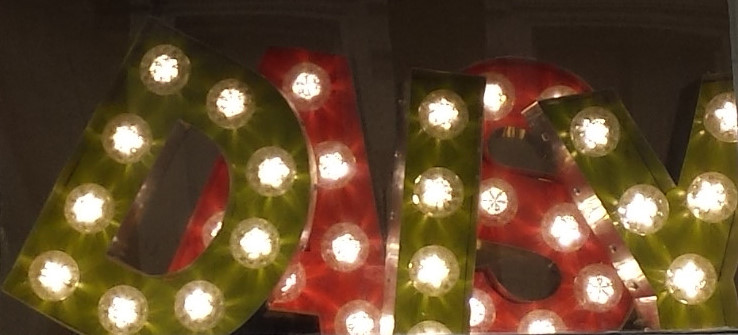 The letters DAISY, illuminated with light bulbs, with the DIY in green and the AS in red