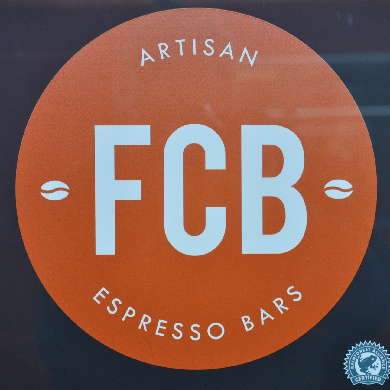 "The FCB Logo: the letters ""FCB"" in white in the centre of an orange circle, with ""Artisan Espresso Bars"" in white around the circumference."