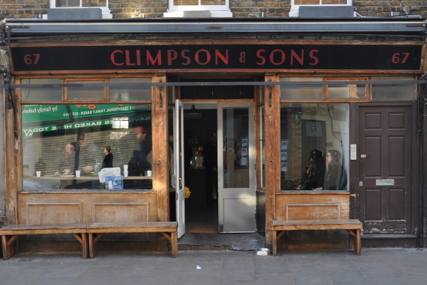 The front of the Climpson and Sons Café, with the recessed door offset to the right and with wooden benches on the pavement in front of the windows.