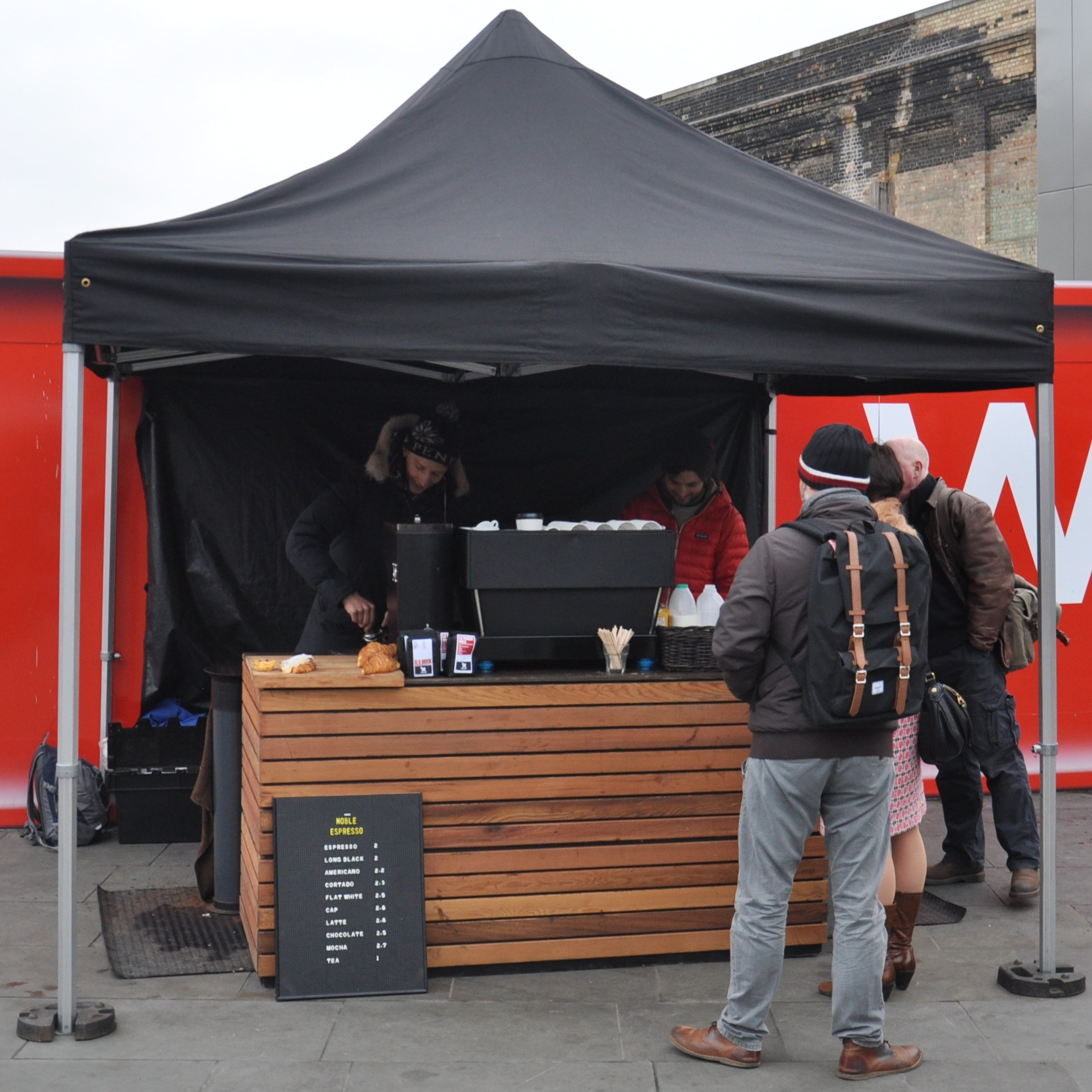 A black pop-up gazebo shelters a wooden counter holding a grinder and espresso machine
