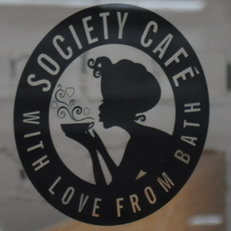 "A black circle surrounding a woman in silhouette blowing on a cup of coffee. The words ""Society Cafe with love from Bath"" are written around the circle."
