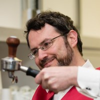 Yours truly holding a portafilter up to check if I've got my tamping level.