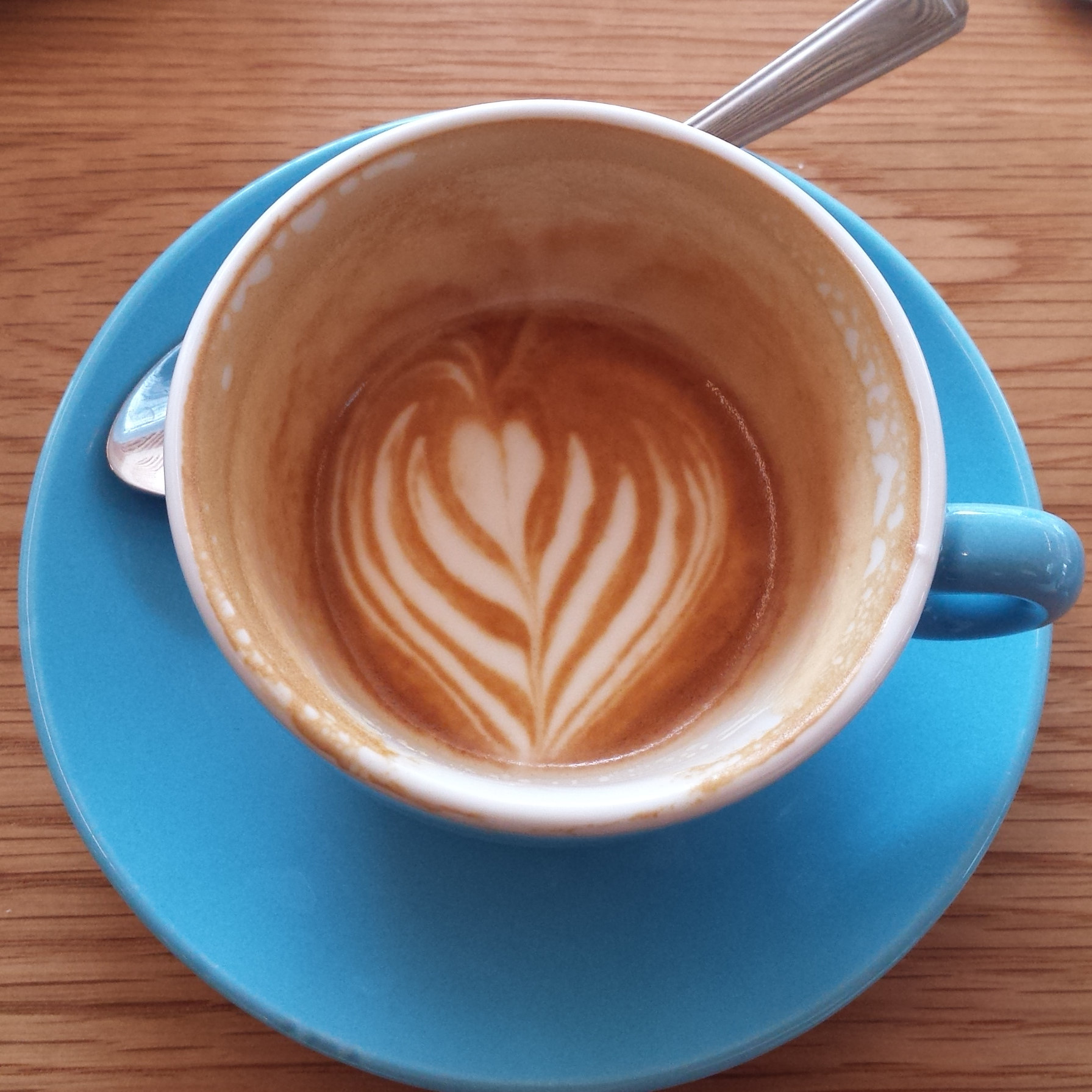 A flat white at Beany Green in Broadgate Circle, with the latte art holding its pattern all the way down to the bottom of the cup.