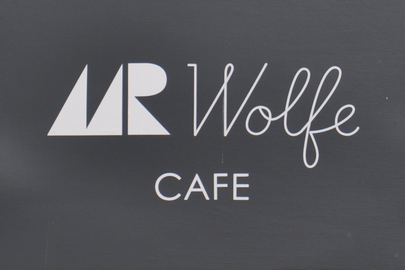 The words Mr Wolfe Cafe in white on black taken from the side of the building.