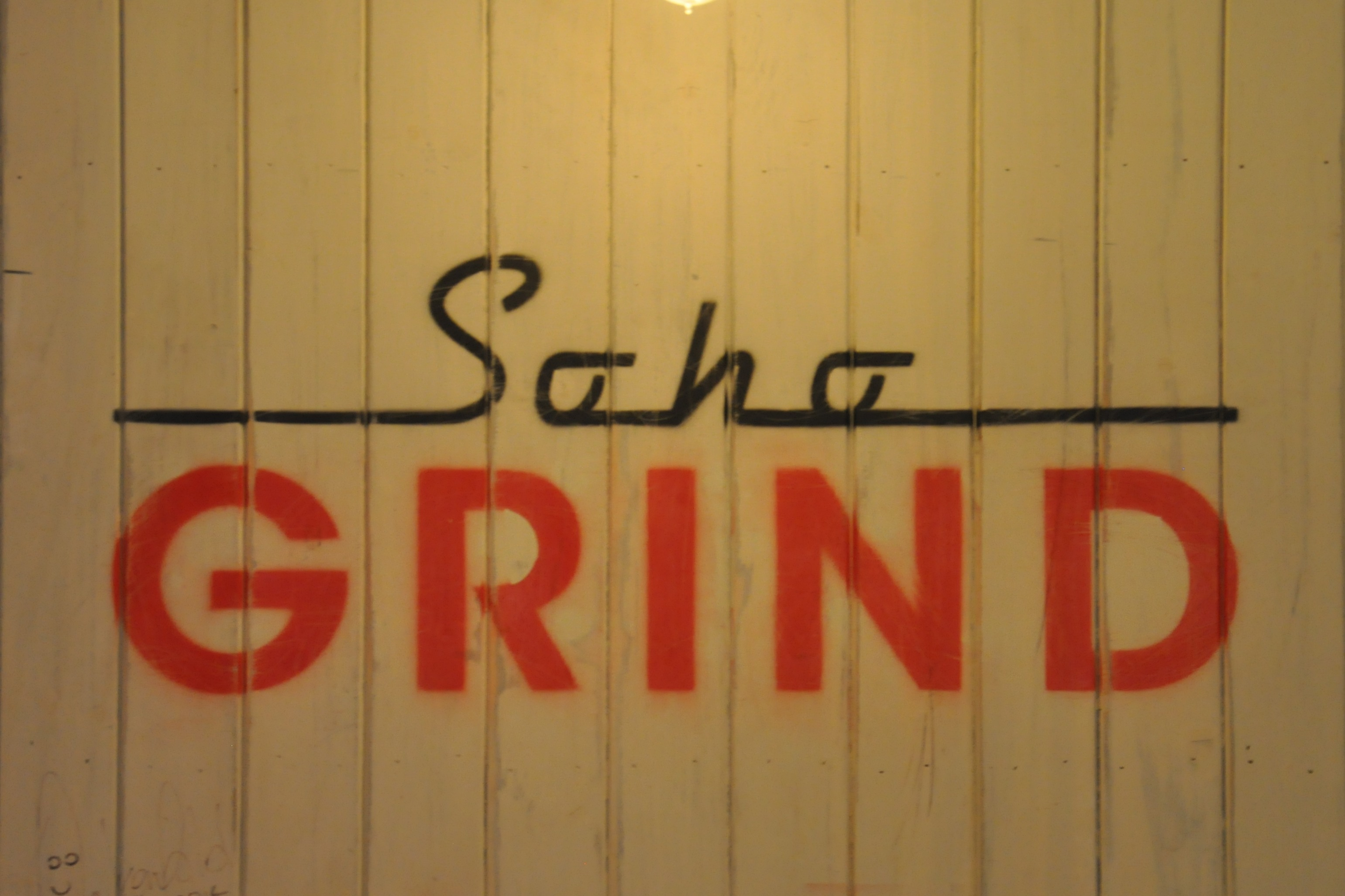 The Soho Grind logo from the back wall of Soho Grind: the word Soho written in black script over GRIND in red capitals.