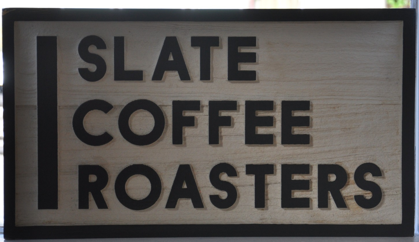 The sign from the window of Slate Coffee Roasters in Seattle: the words 'SLATE COFFEE ROASTERS', one word per line