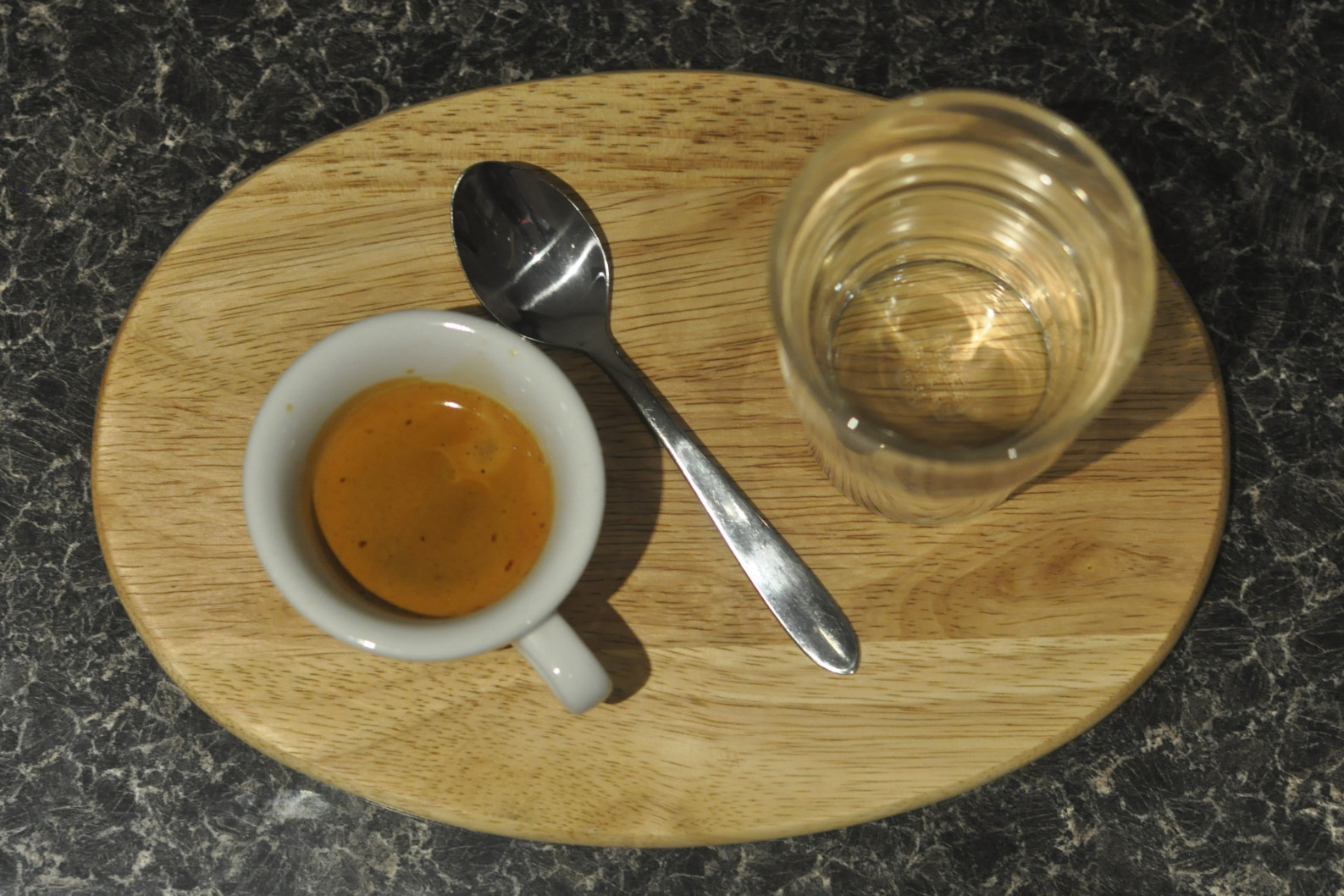 An espresso in a classic white cup, plus a glass of water, on an oval wooden platter, separated by a tea spoon.
