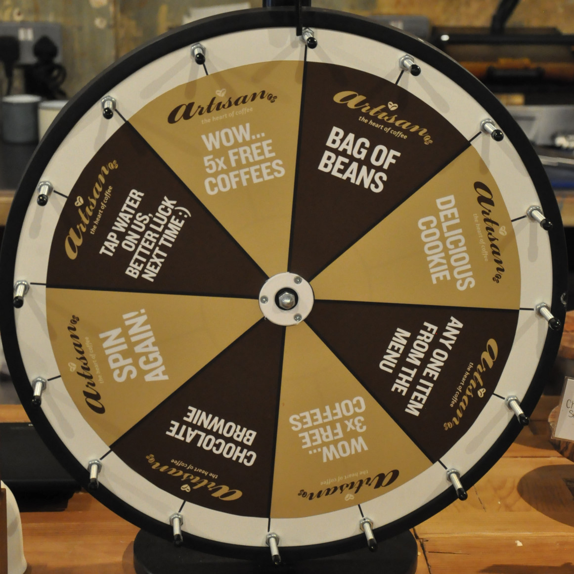 "A ""wheel of fortune"" style wheel from Artisan, Ealing. When a customer gets enough stamps on a loyalty card, instead of getting a free coffee, a spin of the wheel is offered instead, with eight options ranging from a glass of tap water to a bag of beans or five free coffees."