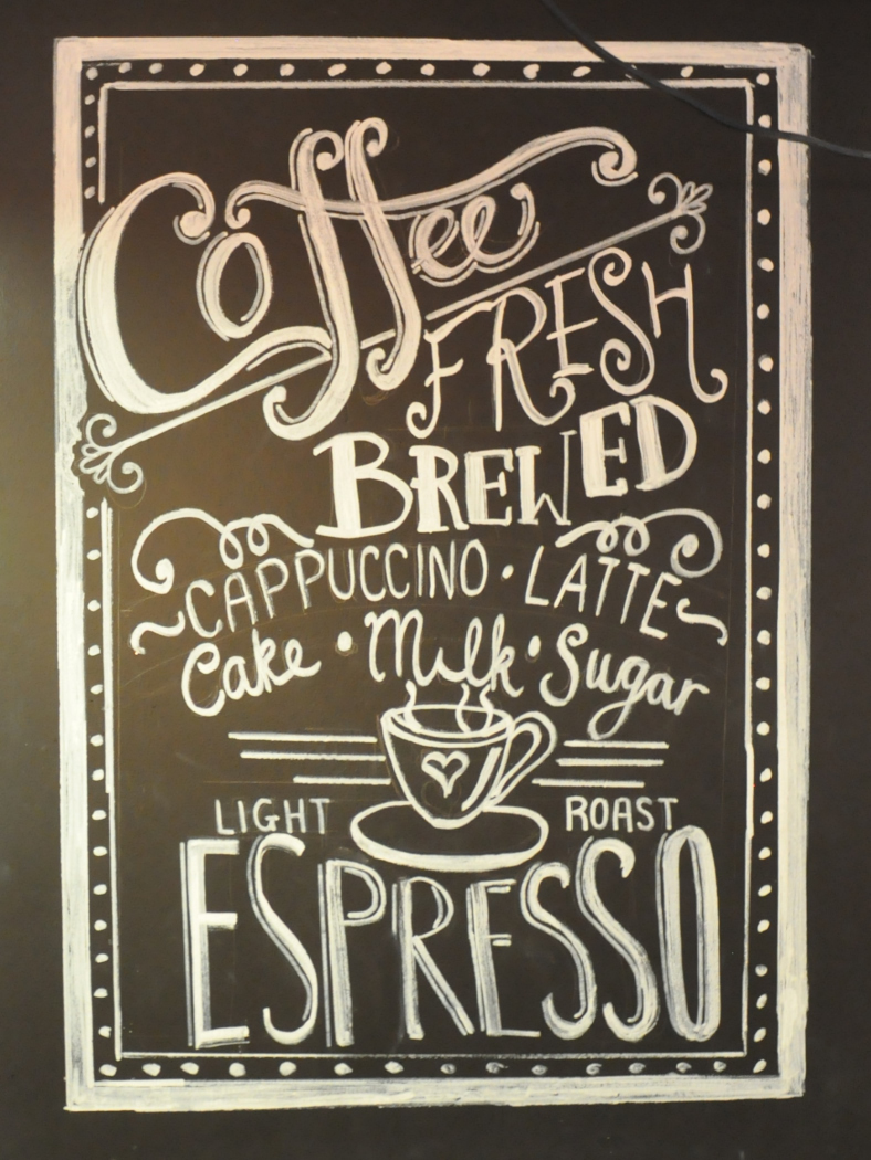 Detail of some of the drawing on the wall behind the bench in Baila Coffee & Vinyl, proclaiming Baila's fresh, brewed coffee and light roast espresso.