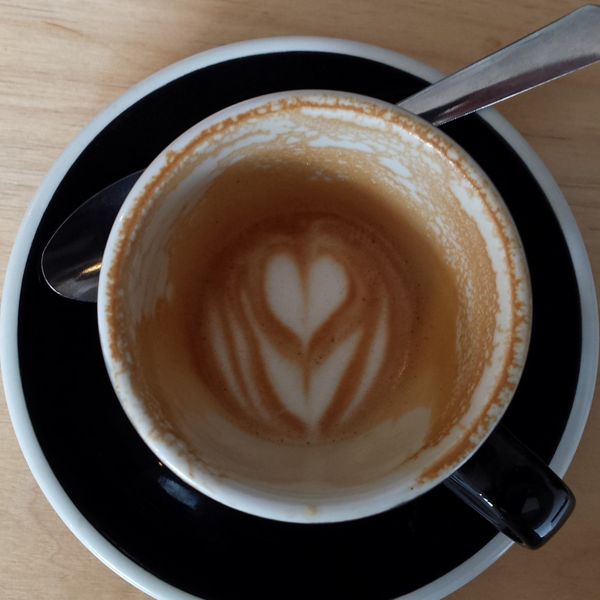 Shot of a tulip cup on a black saucer, taken from above. The coffee is almost gone, but the latte art pattern, a tulip, is still plainly visible in the remainder of the milk in the bottom of the cup.