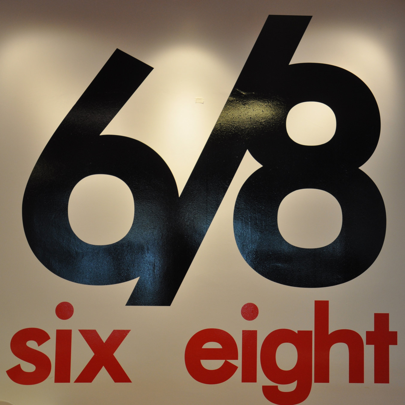 """The 6/8 Kafé logo, the numbers """"6/8"""" in black, with the words """"six eight"""" in red beneath them."""