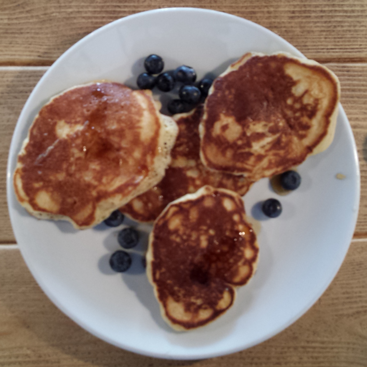 Four mini-American pancakes, in a clover-leaf arrangement, seen from above.