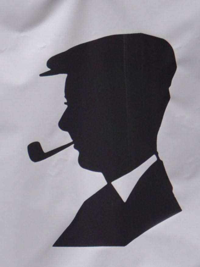 The logo of the Milkman, on Edinburgh's Cockburn Street, a silhouette o the owner's grandfather, seen side-on, wearing a flat cap and smoking a pipe. It was taken from a photograph taken in 1938 at the Empire Exhibition in Glasgow.