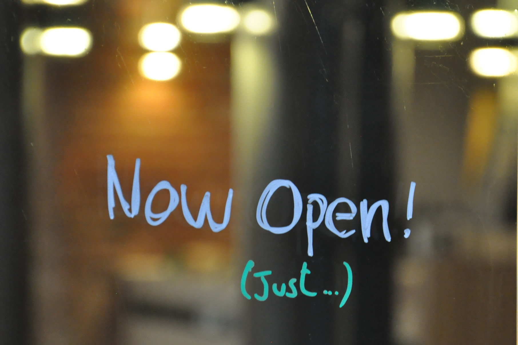 "The words ""Now Open!"" written in blue on the window of Ancoats, with the ""(just...)"" added underneath in green."