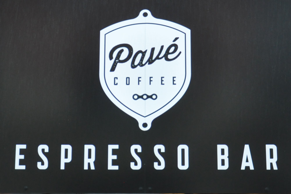 """The words """"Pavé Coffeee"""" in black on a white shield, itself on a black background, with the words """"ESPRESSO BAR"""" in white underneath"""