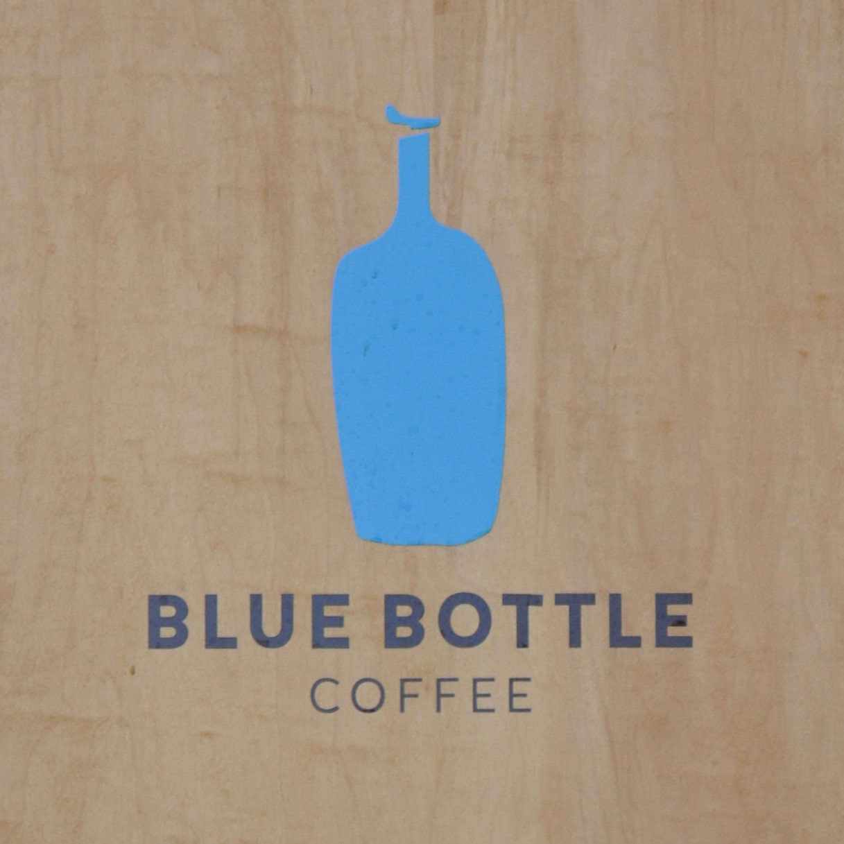 """The Blue Bottle Coffee logo from the A-board outside the Chelsea coffee shop: the outline of a bottle painted in solid blue above the words """"Blue Bottle Coffee""""."""