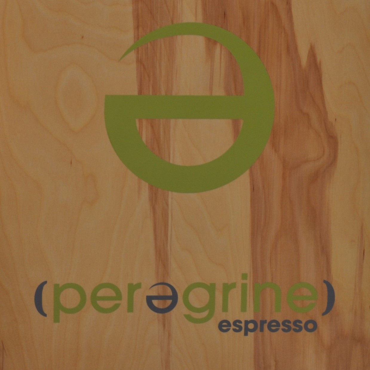 "A large, mirror-image, lower-case e in green over the word ""(perergrine)"", with the brackets and middle 'e' (which is also a mirror-image) in blue. Finally, the word ""espresso"" is in blue in the bottom-right corner."