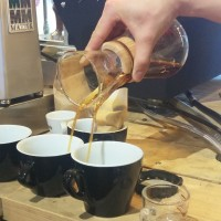 Luke Pochron, at his Brewing Masterclass, Coffee with Luke, simultaneously pouring from a Chemex into two cups.