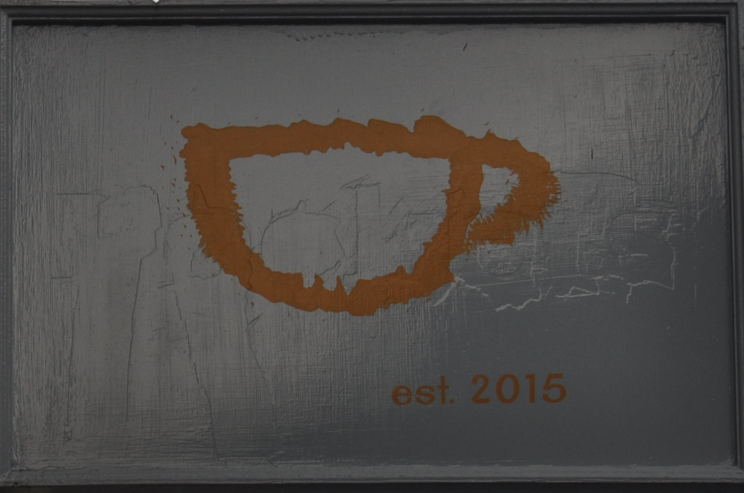 """A stylised outline of a cup in orange paint, with the words """"est. 2015"""" underneath."""