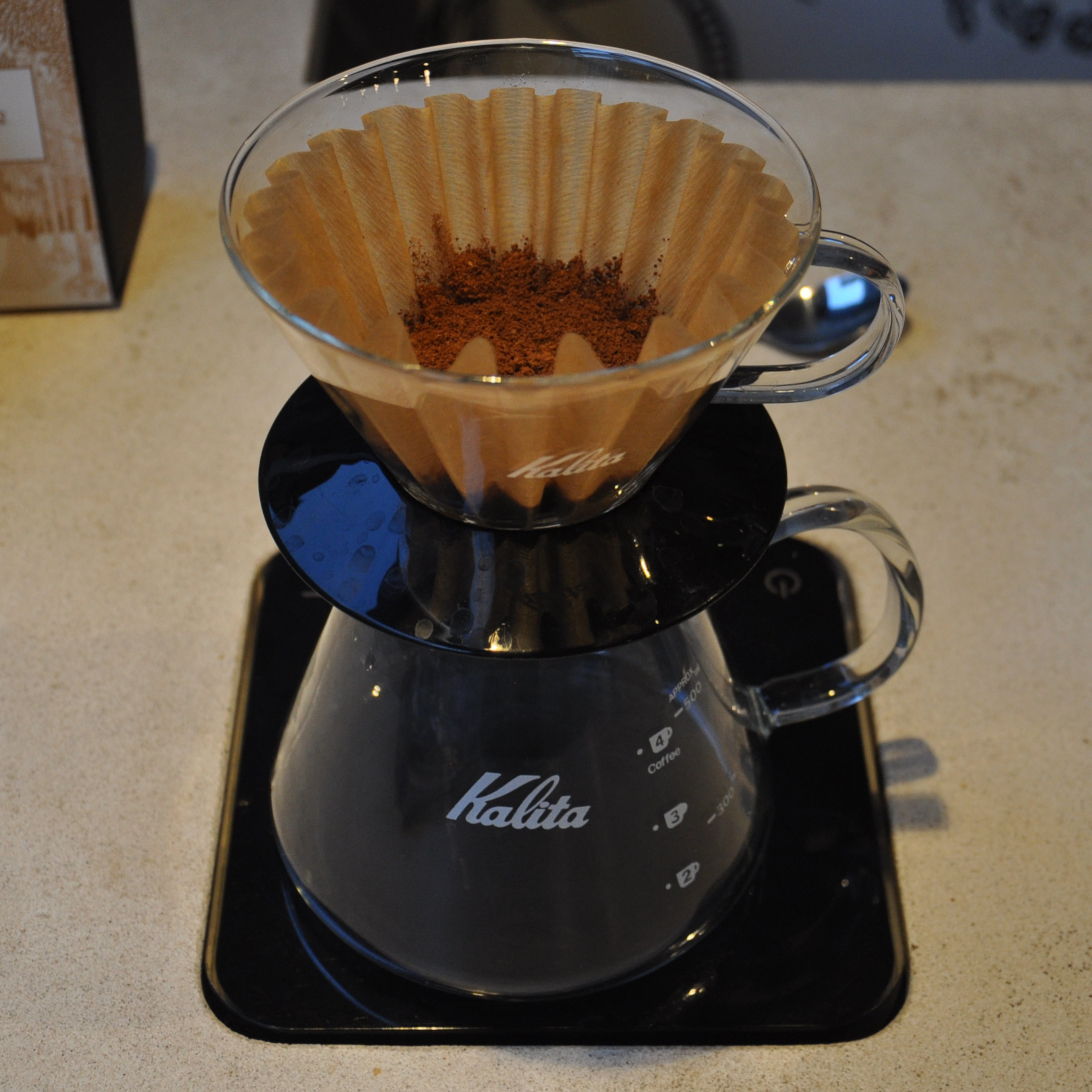 A glass Kalita Wave Filter sitting on a glass Kalita carafe which itself is on a pair of black Acaia scales. The ground coffee has been put in the filter paper, ready for brewing.