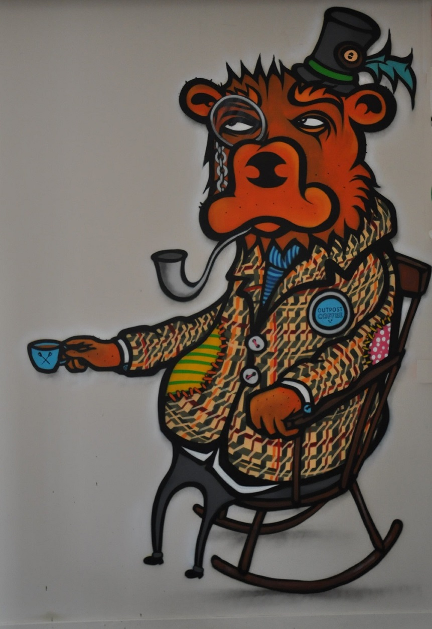 A stylised bear with very short legs sitting in a rocking chair and drinking a cup of espresso. The bear is wearing a smoking jacket, (small) top hat and a monocle and is smoking a pipe.