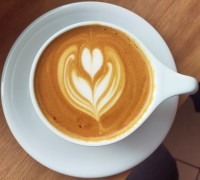 A flat white, seen from above, with tulip pattern latte art in a white cup on a white saucer.