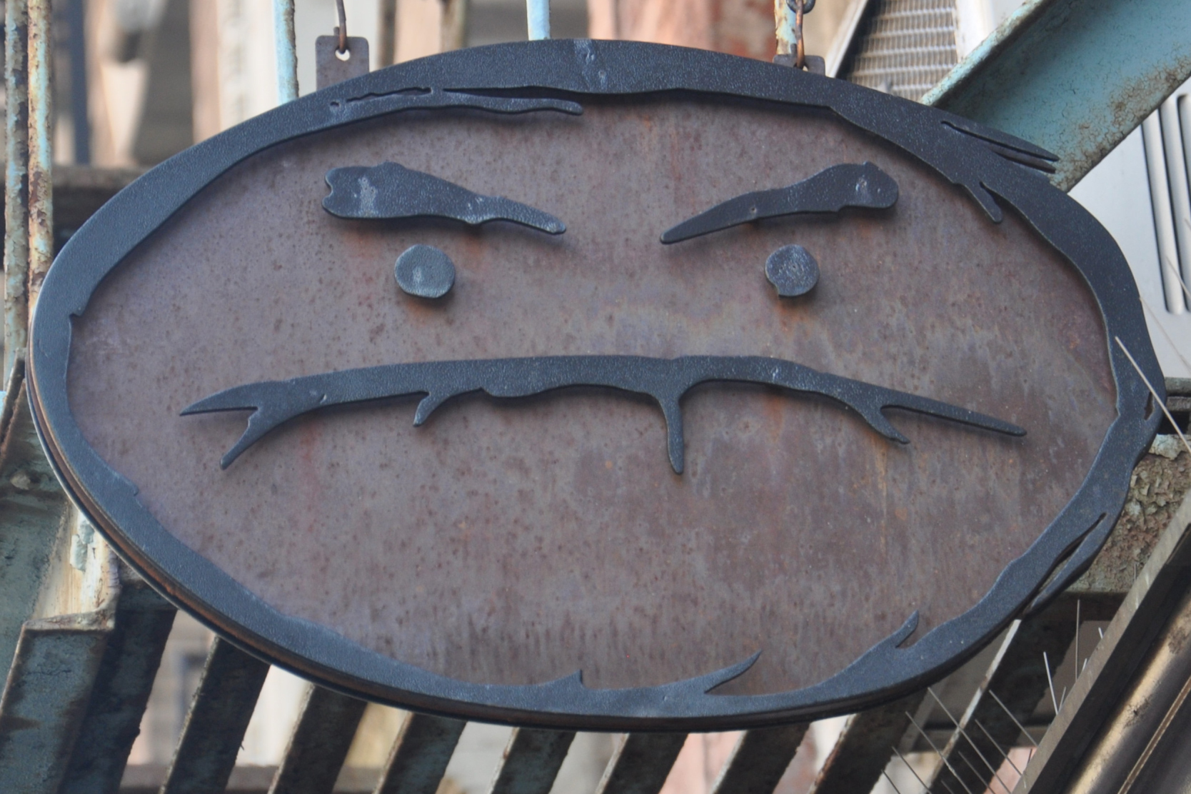 The somewhat unwelcoming Cafe Grumpy sign: an elongated oval, stylised as a face, with frowning eyebrows and a downturned mouth.