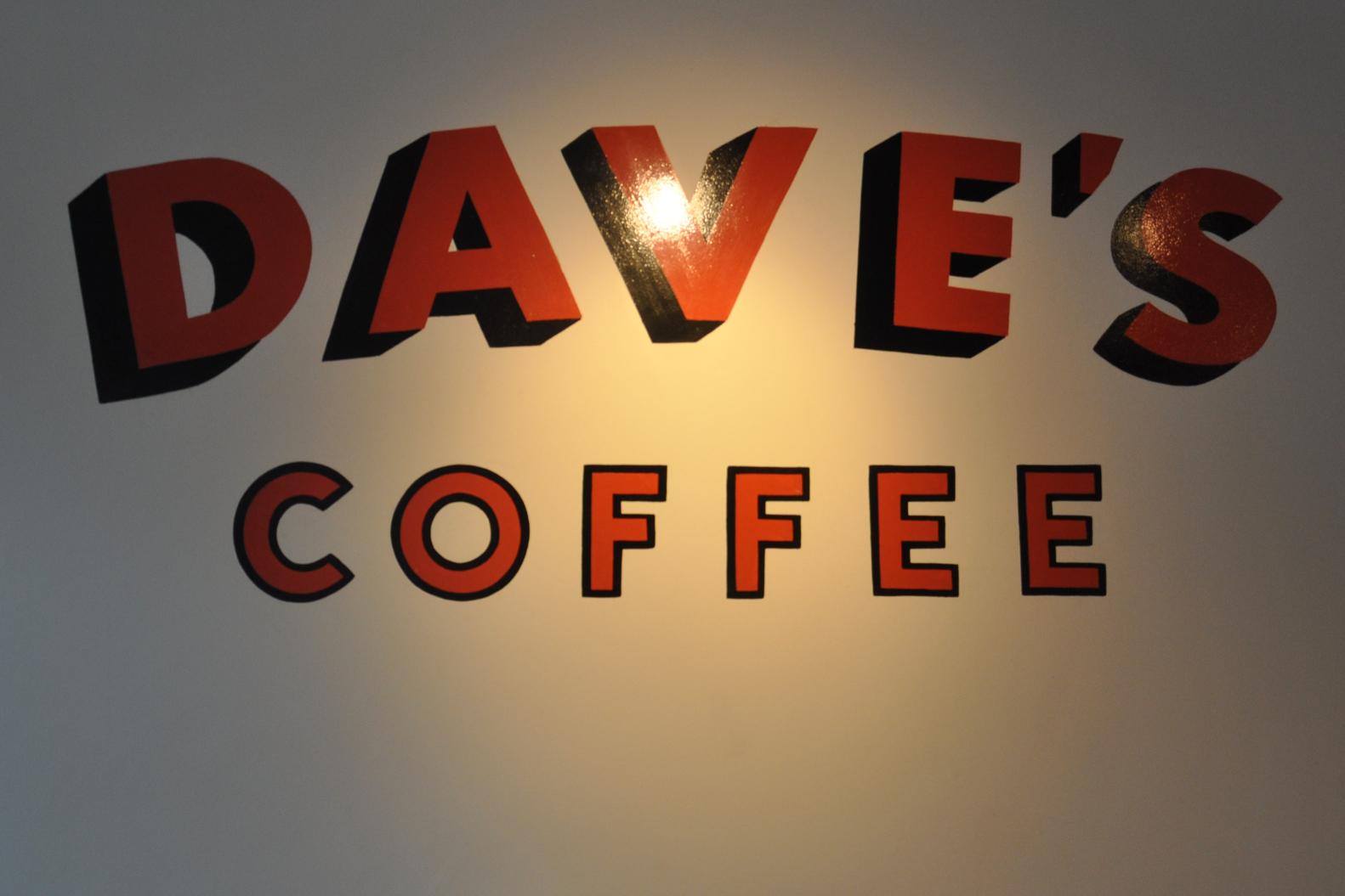 "The words ""Dave's Coffee"" in red on a white wall."