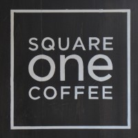 """The words """"SQUARE one COFFEE"""" one word per row, white on black inside a white square."""