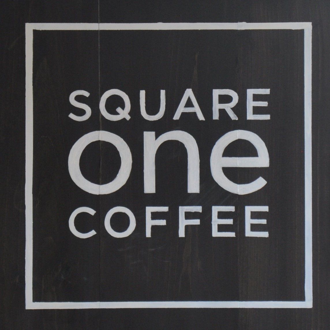 "The words ""SQUARE one COFFEE"" one word per row, white on black inside a white square."