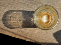A cortado, holding its latte art to the bottom of the glass, sparkling in the sun at Sweetleaf on Jackson Avenue.