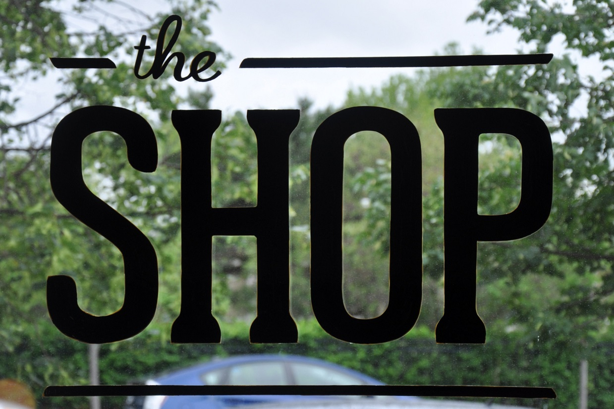 "The words ""The Shop"" painted in black on the window."