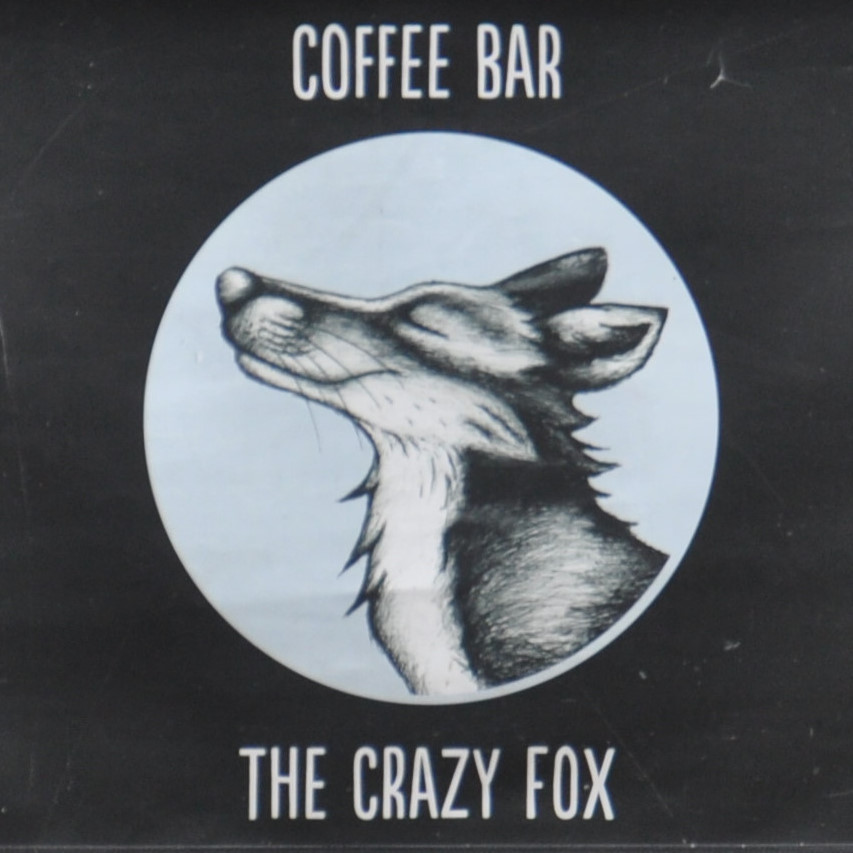 """A drawing of a very smug-looking fox in a circle on a black background, with the words """"Coffee Bar"""" above and """"The Crazy Fox"""" below."""