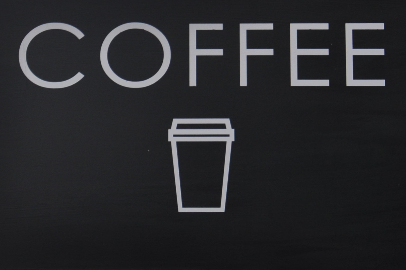 "The word ""COFFEE"" i white on black, over a stylised outline of a takeaway coffee cup, again in white on black."