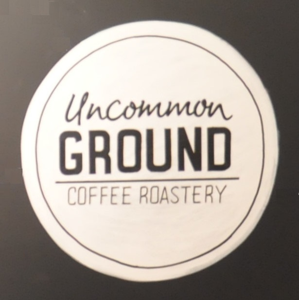 "The word ""Uncommon GROUND COFFEE ROASTERY"" written in black inside a white circle on a black background."