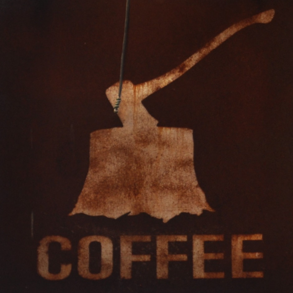 A square with the motif of an axe buried head-first in a tree-trunk above the word COFFEE
