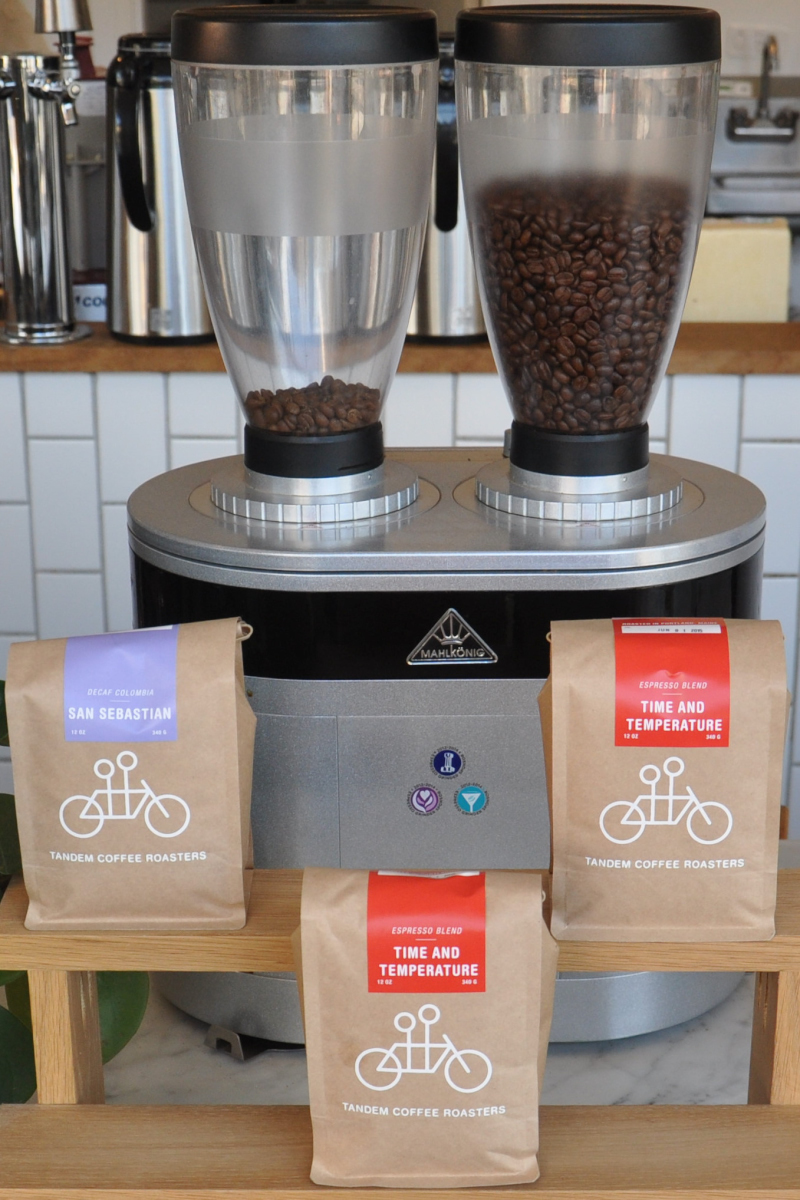 A dual-hopper Malhkonig Coffee Grinder with three bags of Tandem Coffee Roasters coffee in front of it, each with Tandem's logo of a stick-figure tandem bicycle.