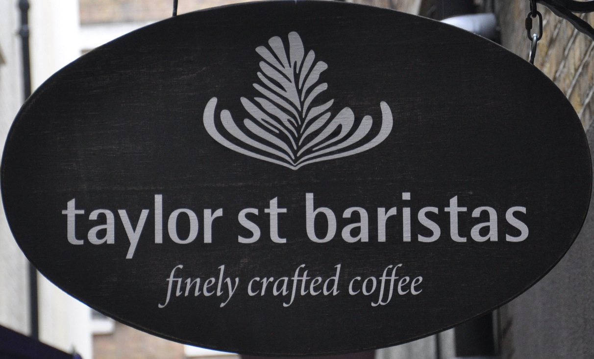 "A latte-art style fern above the words ""taylor st baristas"" with ""finely crafted coffee"" written underneath, all in white on a black oval."