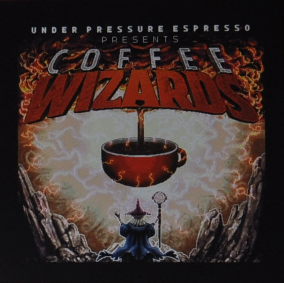 A wizard is shown underneath a large coffee cup. This is surrounded by lightning and is being filled by a stream of coffee from above.
