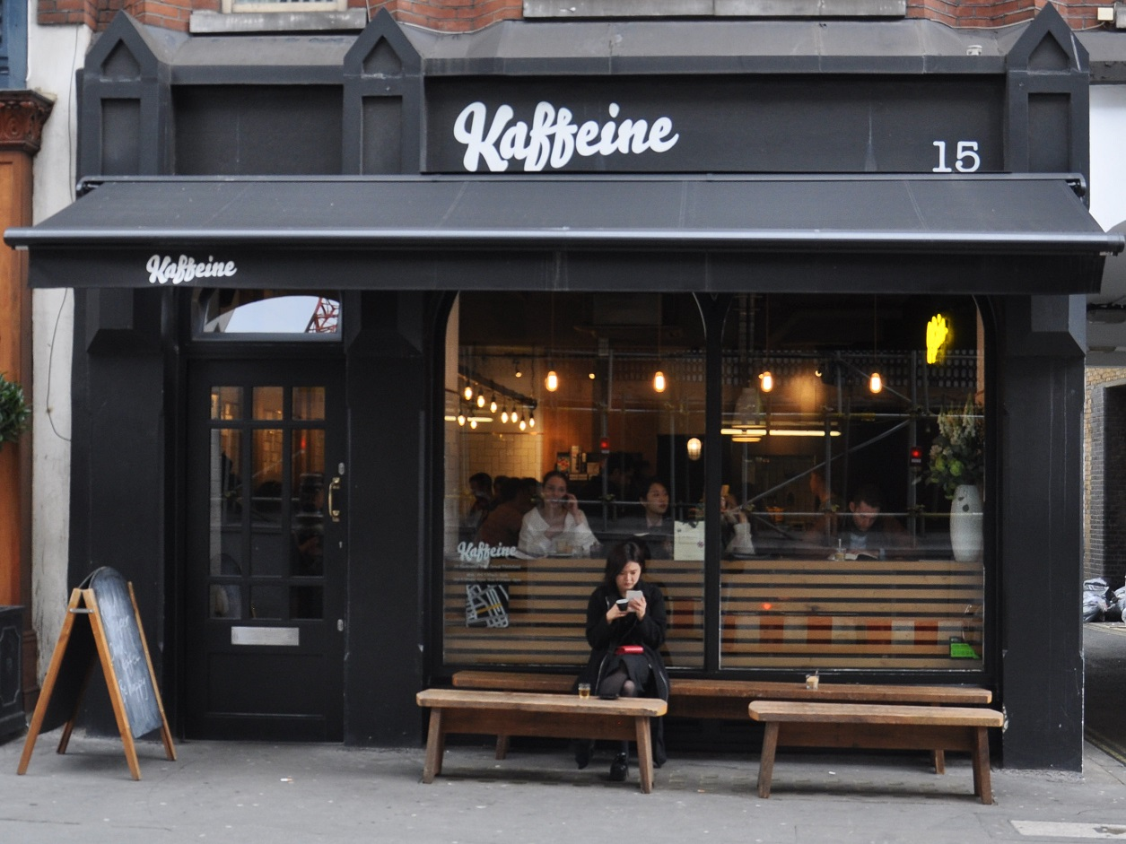 The front of Kaffeine, door to the left, windows to the right, with a pair of benches in front of the window acting as tables.