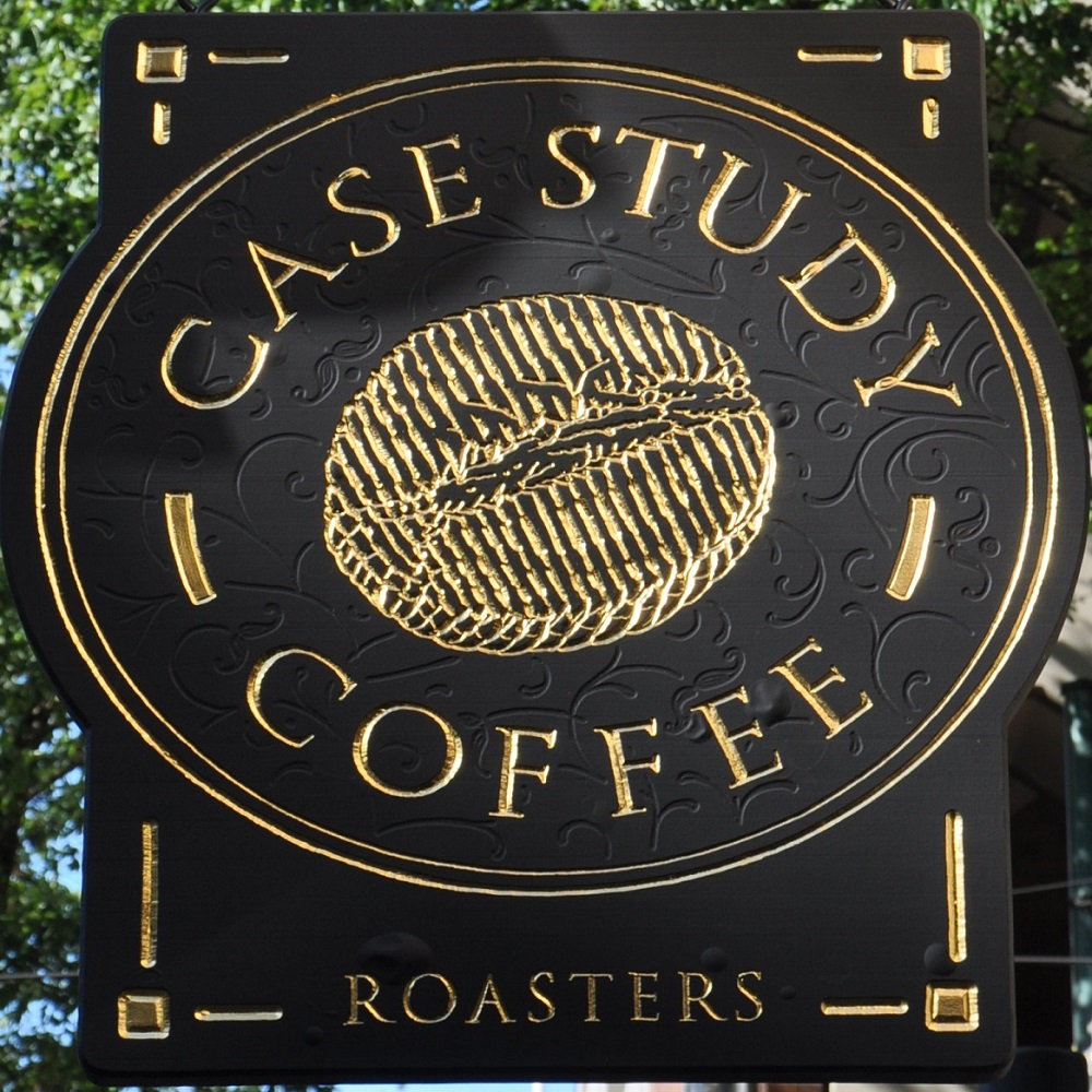The words Case Study Coffee in gold on black written in an oval around a line-drawing of a coffee bean.