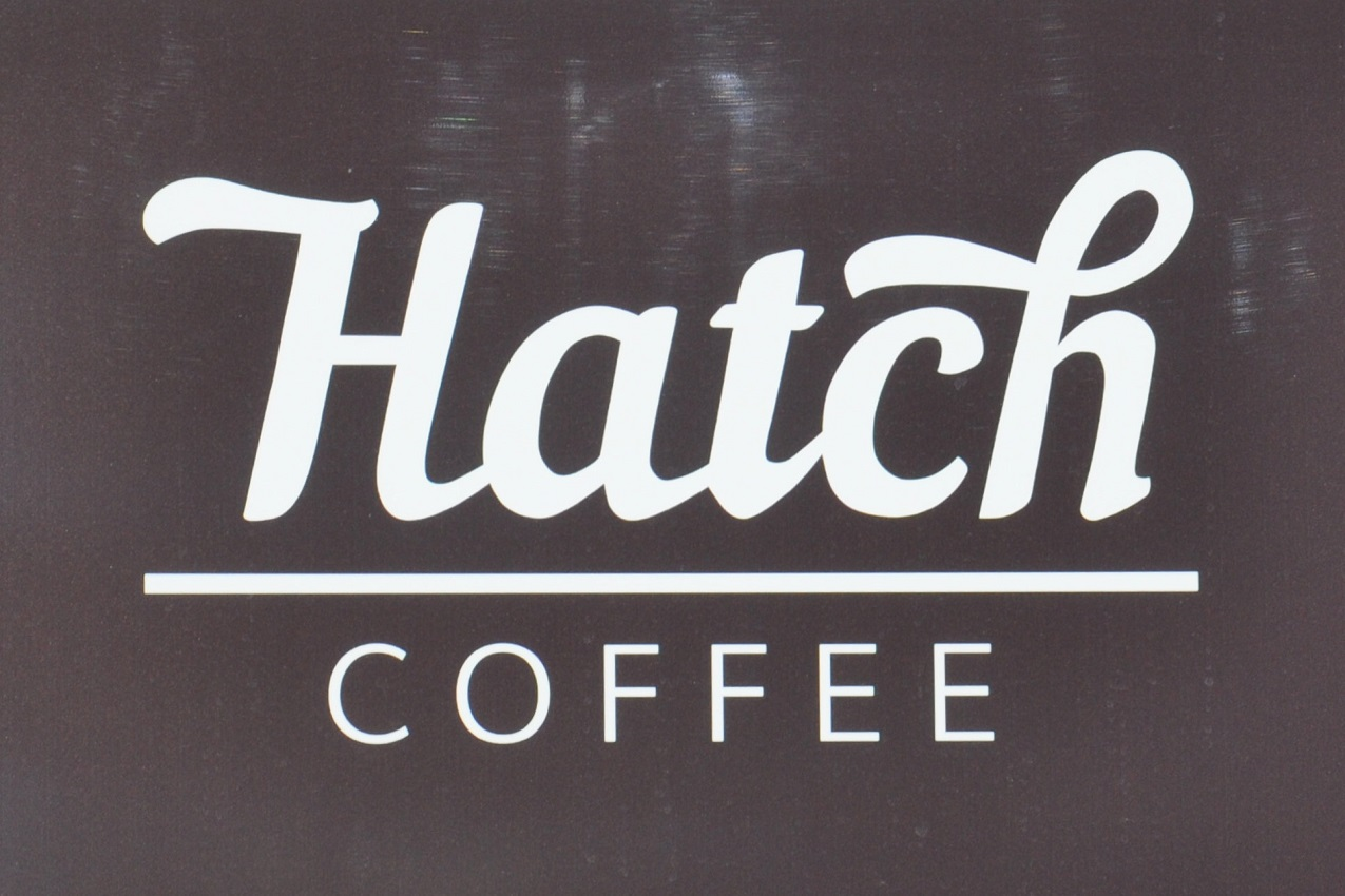 "The word ""Hatch"", written in cursive script in white on black, over the word ""COFFEE"", separated by a horiztonal white line."
