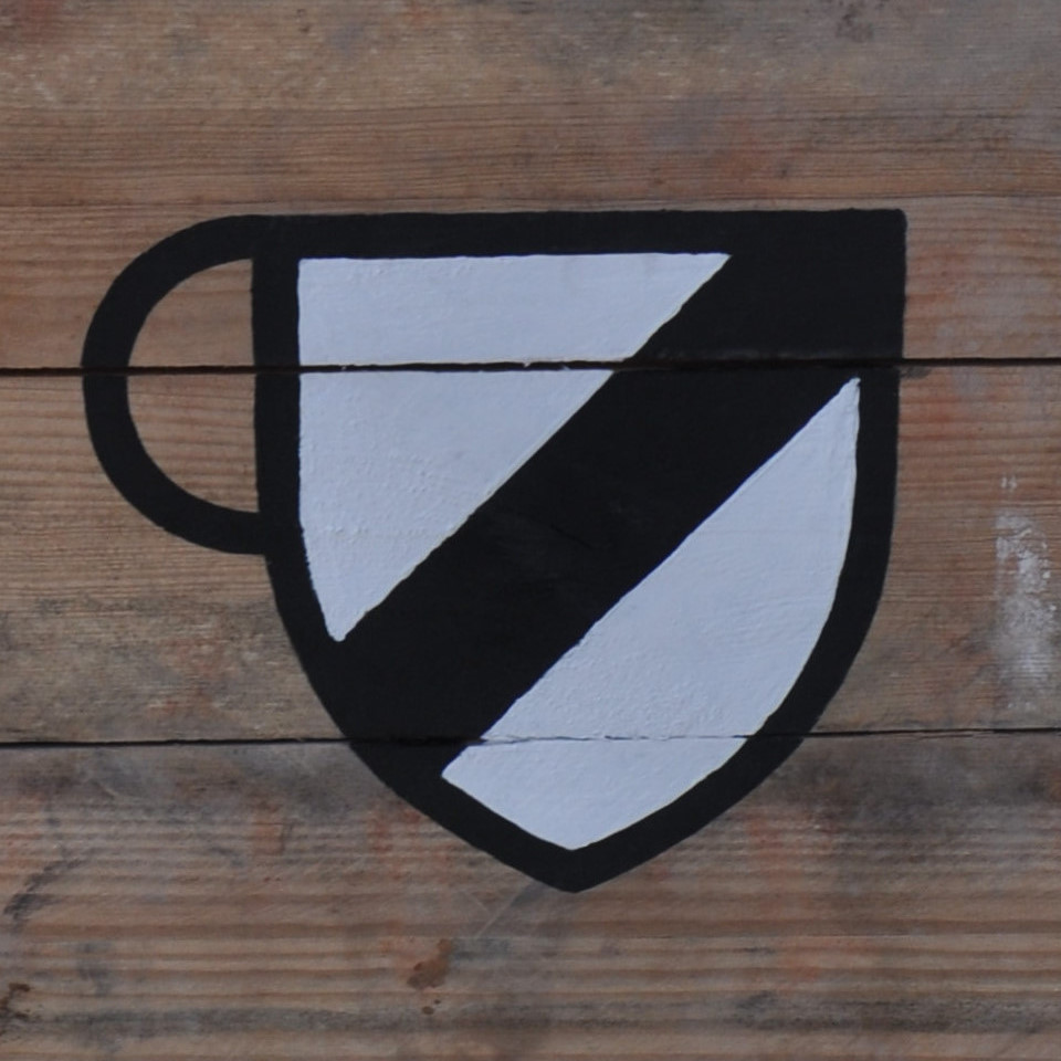 An old-fashioned, heraldic shield, in white, with a black diagonal line running through it, bottom left to top right, with a handle added on the left to turn it into a coffee cup