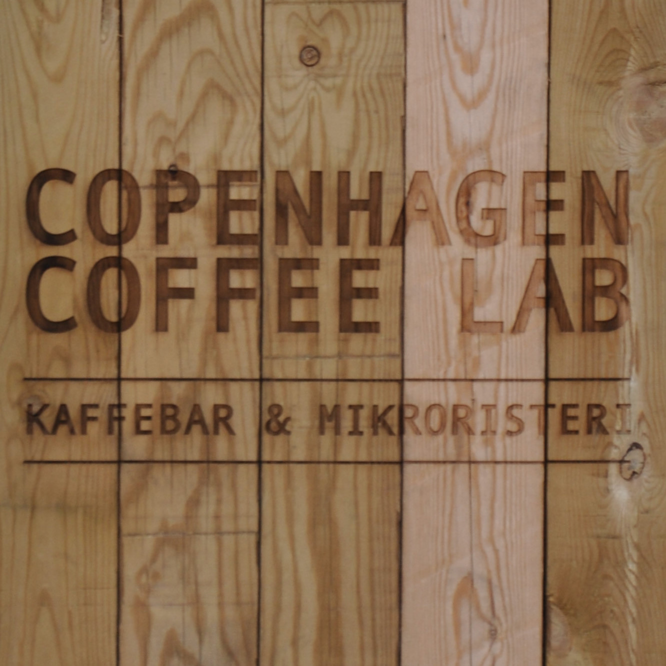 """Copenhagen Coffee Lab"" written above ""Kaffebar & Mikroristeri"" on an A-board made of five, vertical wooden planks."