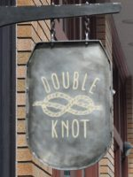 "The words ""Double Knot"" written with the picture of a piece of rope tied into a Double Knot in the middle."